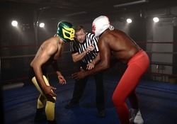 Two masked wrestlers prepare to fight