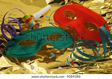 Two masks on golden background with confetti, streamers and noisemaker