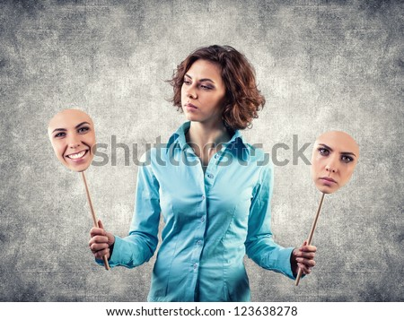 Two masks with different emotions in hands of the girl