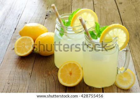 Two mason jar glasses of homemade lemonade on a rustic wooden background