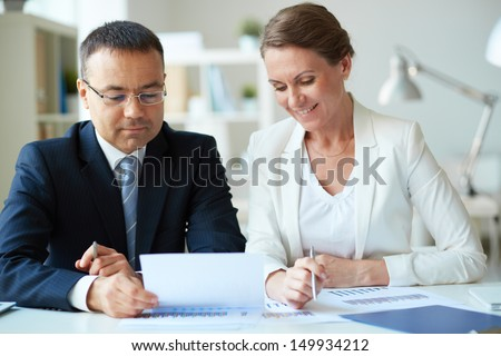 Two mature business partners looking at document in office