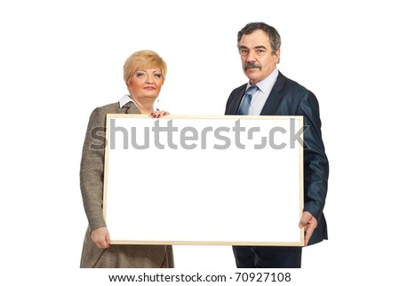 Two mature business people holding a blank banner isolated on white background