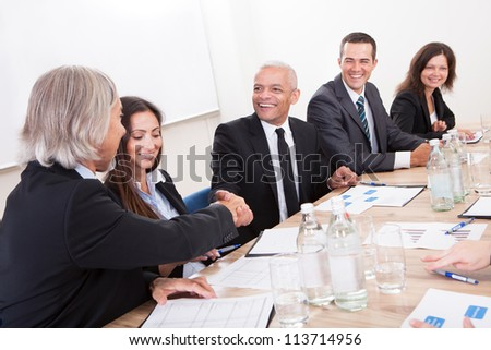 Two Mature Businessman Shaking Hands In Meeting - stock photo