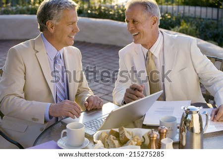 Two mature businessmen sitting at outdoor restaurant table, one man using laptop, smiling, side view