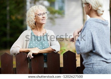 Two mature female neighbours talking through fence about everyday life stuff