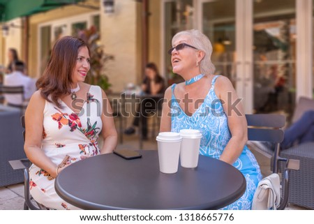 Two mature ladies enjoy a cup of coffee at the outdoor cafe.