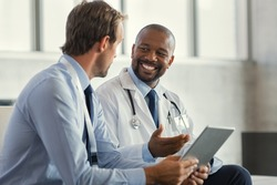 Two mature smiling doctors having discussion about patient diagnosis, holding digital tablet. Representative pharmaceutical discussing case after positive result with happy doctor about new medicine.