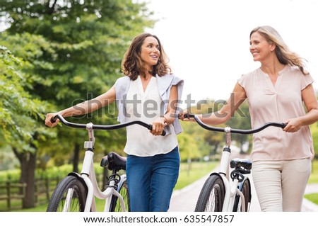 Two mature women in conversation while walking with bicycle at park. Happy beautiful senior women walking in the park with bicycles in a spring time. Friends holding bikes and talking to each other.