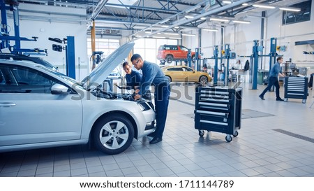Two Mechanics in a Service are Inspecting a Car After They Got the Diagnostics Results. Female Specialist is Comparing the Data on a Tablet Computer. Repairman is Using a Ratchet to Repair the Faults. Foto stock ©