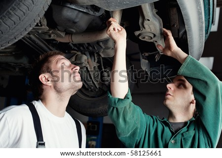 Two mechanics repairing car in garage under the car.