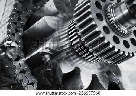 two mechanics, workers with large gears and cogs machinery
