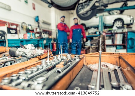 Two mechanics working on a car . close up on mechanic tools
