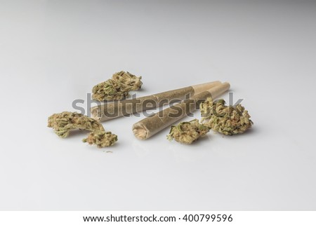 Two medical cannabis rolled joints with dried marijuana buds around on white background from side