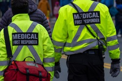 Two medical first responders walking in a street among a crowd of people.One of the EMTs is carrying a red first aid bag.The emergency personnel have bright yellow reflective jackets with grey stripes
