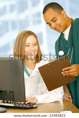 two medical people looking at same clip board and smiling. the woman is sitting down and the nurse is standing