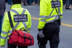 Two medical responders walking in a street with bright yellow coats with the words medical first responder on a black background with grey lettering. One medical officer is carrying a first aid bag.