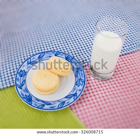 Two melting moment biscuits on a decorated small plate placed on blue, green and red drapery