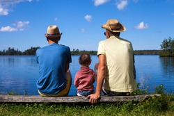 Two men and a toddler at a lake during nice summer day