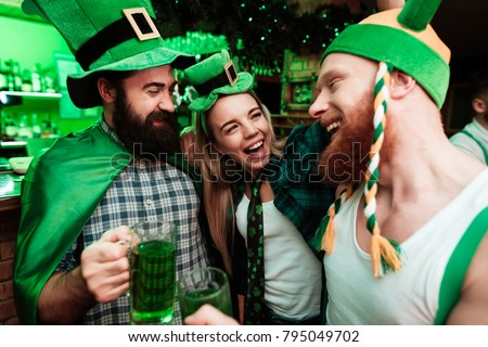 Two men and girl in carnival hats drinking beer at the bar. They celebrate St. Patrick's Day. They are having fun.