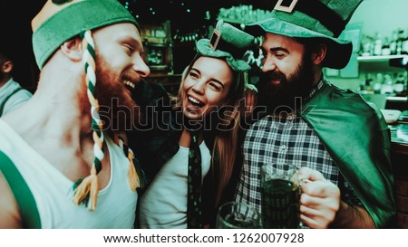 Two Men And Girl In Carnival Hats Drinking Beer. St Patrick's Day Celebrating Concept. Bar Counter. Bearded Males. Good Festive Mood. Bright Lights. Club Visitors. Having Fun. Resting Together.