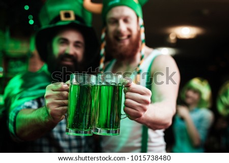 Two men are drinking beer in a bar. He celebrates St. Patrick's Day with friends.