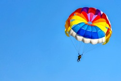 Two men are gliding using a parachute on the background of the blue sky.