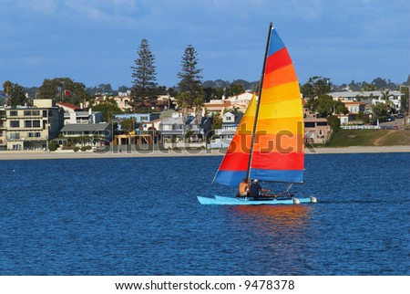 Two men are sailing a yacht with colorful sail in Mission Bay, San Diego, California.