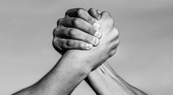Two men arm wrestling. Arms wrestling. Hand, rivalry, vs, challenge, strength comparison. Two muscular hands.Friendly handshake, friends greeting, teamwork Black and white