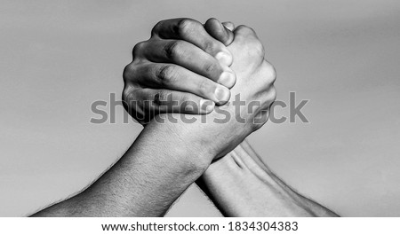 Two men arm wrestling. Arms wrestling. Hand, rivalry, vs, challenge, strength comparison. Two muscular hands.Friendly handshake, friends greeting, teamwork Black and white ストックフォト ©