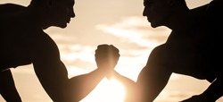 Two men arm wrestling. Silhouette of hands that compete in strength. Rivalry, closeup of male arm wrestling. Rivalry, vs, challenge, hand wrestling.