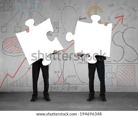 Two men assembling puzzles with business doodles on concrete wall Stock photo ©