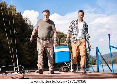 Two men carrying their cool box