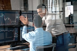 Two men colleagues traders sitting at desk at office monitoring stock market getting profit achieving success giving high five doing great job laughing happy trading concept