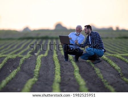 Two men crouching in soy field using computer. Farmer and businessman looking at sprout, pointing explaining using modern technology computer in agriculture.  Сток-фото ©