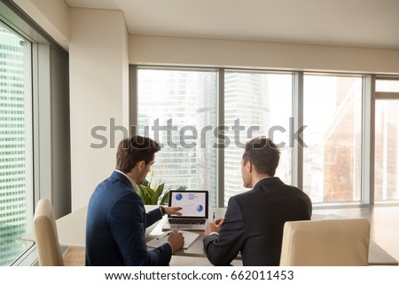 Two men discussing company growth, looking at rising graph on laptop screen, using easy accounting software for small business, stock traders analyzing market, pointing at charts on monitor. Rear view