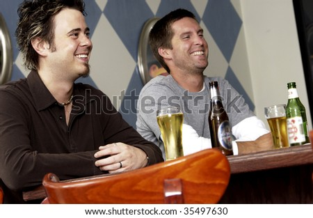 two men drinking at bar - stock photo