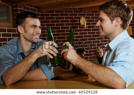 Two men drinking beer in bar, clinking bottles, smiling, women talking in background.?