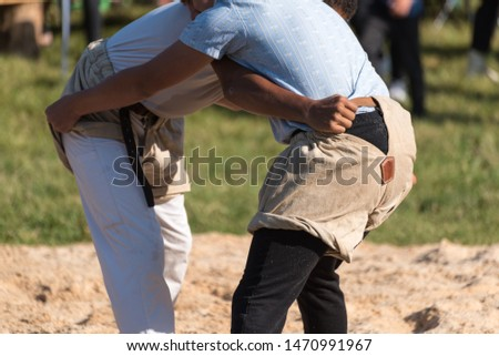 Two men during traditional swiss wrestling in wrestling trousers and edelweiss shirt fighting in the sawdust