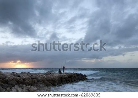 Two men fishing at dawn in Bali, Indonesia
