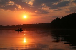 Two (2) men fishing in a boat in lake during sunset. Geographical location: Europe