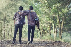 Two men, friends walking on road with guitar on hand, beautifull nature