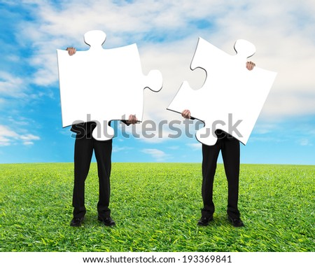 Two men holding blank puzzles on grass ground with blue sky Stock photo ©
