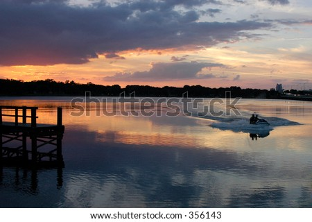 Two men in a boat are coming in at sunset creating a wake in the glassy reflection of the sky.
