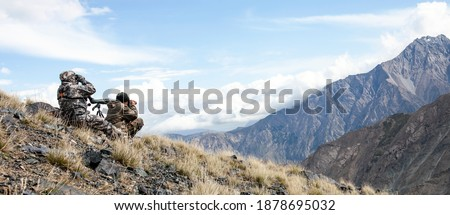 Two men in camouflage conduct surveillance high in the mountains. Hunters use optics to search for hunting objects on the mountainside.  Foto d'archivio ©