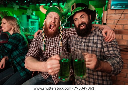 Two men in carnival caps celebrate St. Patrick's Day. They have fun at the bar. They keep glasses with beer.