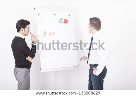 two men in front of a flipchart during a presentation.