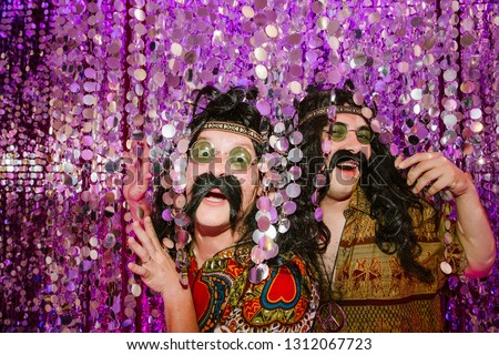 Two men in hippie costumes with false mustaches and hair peeking out from festive decorations with funny faces.