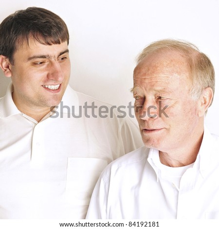 Two men in living room standing against the wall  smiling