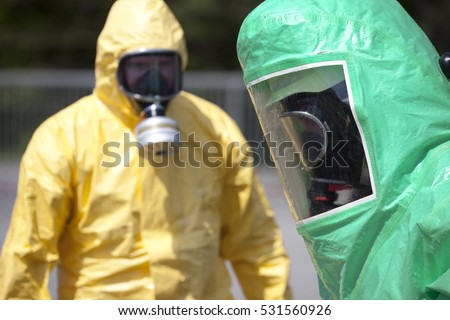 Two men in protective gear cleaning up after chemical or radiation accident. The gear protects against contamination with radioactive particles, Alpha radiation and partially Beta radiation.