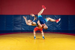 Two men in sports wrestling tights and wrestling during a traditional Greco-Roman wrestling in fight on a wrestling mat. Wrestler throws his opponent's chest through